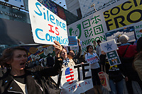 "A woman holds a sign that reads, ""Silence is Complicity"" at the Vote Out the Scandal rally at Hachiko Square, Shibuya, Tokyo, Japan. Sunday November 5th 2017. Timed to coincide with President Trumps visit to Japan, About 120 Americans living in Japan and some local Japanese  protested together from 2pm to 4pm to encourage US citizens to register to vote in future elections and call on the US government to honour it responsibilities to the American people,."