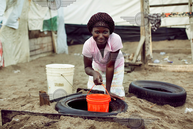 Esther Ogunleke pulls water from a well.  Like millions of Lagos residents, Esther lives in a makeshift shack on land that she does not own.