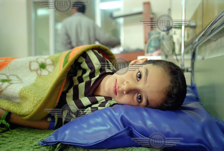"""(February 1998) Nine year old Haiman Sabri at the Saddam hospital in Baghdad. <br /> According to his doctor Haiman had a curable infection, but due to lack of anti biotics suffered life threatening complications.  <br /> Due to UN sanctions the hospital was lacking many medicines, and the civilians suffered due to lack of food as well. <br />  Former U.N. Humanitarian Coordinator in Iraq Denis Halliday estimated the resulting deaths : """"Two hundred thirty-nine thousand children 5 years old and under"""" as of 1998.<br /> <br /> The sanctions against Iraq were a near-total financial and trade embargo imposed by the United Nations Security Council on the Iraqi Republic.<br /> <br /> <br /> ©Fredrik Naumann/Felix Features"""