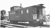 Side-end view of long caboose #04343 at Alamosa, flying herald.<br /> D&amp;RGW  Alamosa, CO  Taken by Ward, Bert H. - 7/10/1946