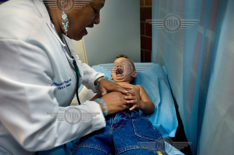 A Cuban doctor examines a distressed child at a health clinic, part the Mission Barrio Adentro project. This aims to offer poor Venezuelans access to health and medical facilities and is funded from oil revenues. The project employs 30, 000 Cuban health professionals: doctors, dentists, physiotherapists and technicians etc.