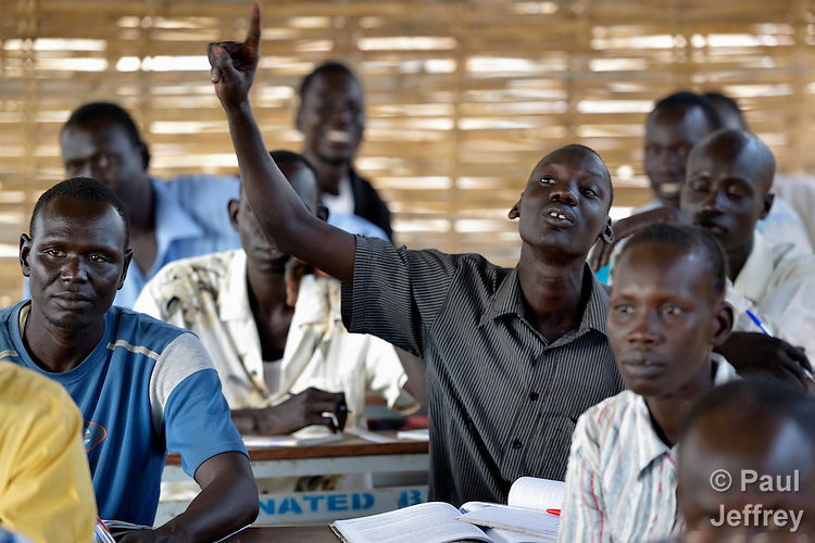 A teacher raises his hand during a continuing education class for displaced teachers in Agok, a town in the contested Abyei region where tens of thousands of people fled in 2011 after an attack by soldiers and militias from the northern Republic of Sudan on most parts of Abyei. The class is conducted by Solidarity with South Sudan, an international network of religious orders and congregations assisting the newly independent country of South Sudan to train teachers, health care personnel, and pastoral workers. .