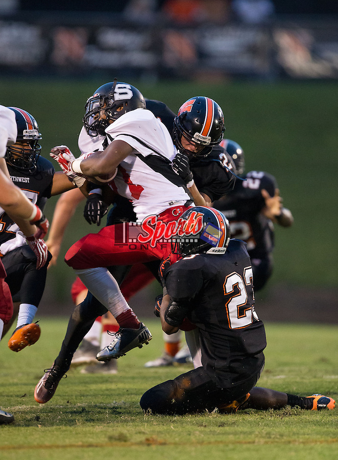 Jamorya Cousin (17) of the South Rowan Raiders is hit by Isaiah Williams (23) and Anthony Caldwell (25) of the Northwest Cabarrus Trojans during first quarter action at Trojan Stadium September 12, 2014, in Concord, North Carolina.  (Brian Westerholt/Sports On Film)