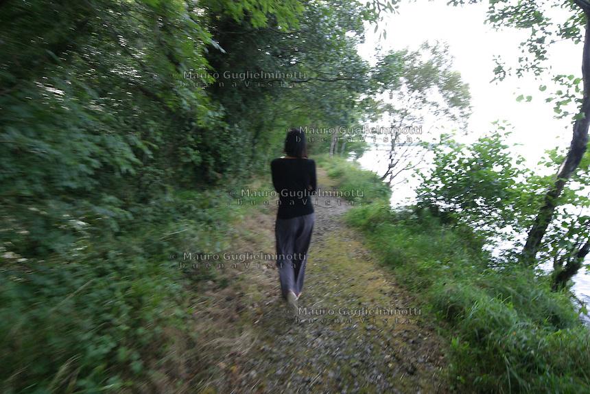 Ragazza bruna di spalle si allontana in un bosco, Brunette girl from behind leaves in a forest  fille s'éloigne dans un bois