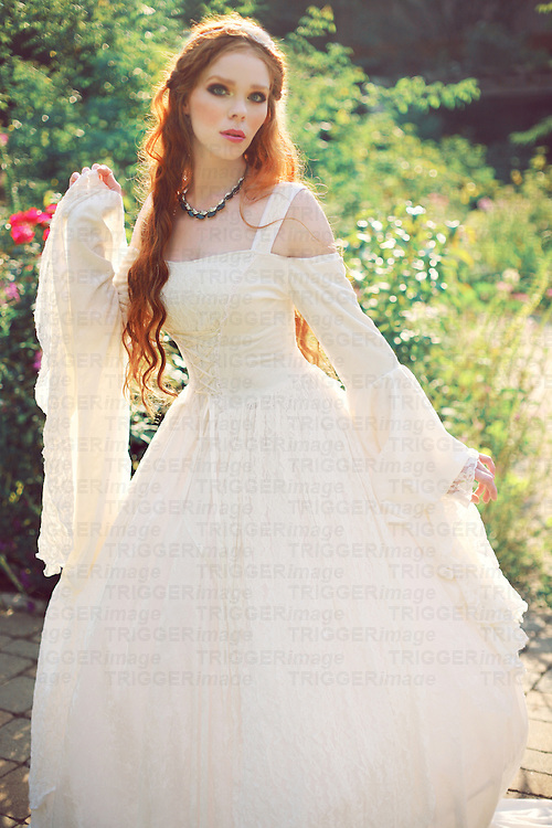 A beautiful young redheaded woman in her 20s looks like a traditional bride with a logn fancy gown, in a pretty garden
