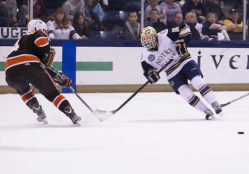 March 15, 2013:  Notre Dame center T.J. Tynan (18) passes the puck during NCAA Hockey game action between the Notre Dame Fighting Irish and the Bowling Green Falcons at Compton Family Ice Arena in South Bend, Indiana.  Notre Dame defeated Bowling Green 1-0 in overtime.