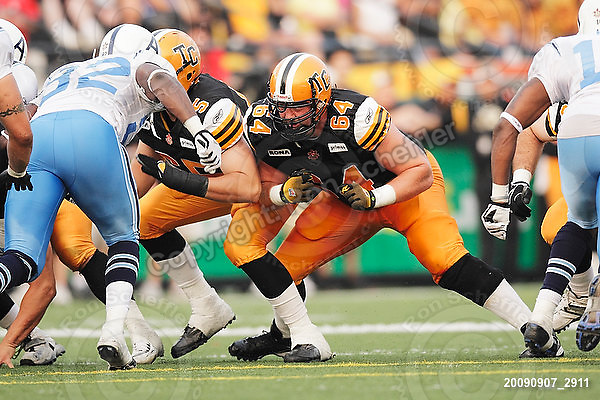 September 7, 2009; Hamilton, ON, CAN; Hamilton Tiger-Cats offensive lineman Simeon Rottier (65) offensive lineman Dan Goodspeed (64). CFL football - the Labour Day Classic - Toronto Argonauts vs. Hamilton Tiger-Cats at Ivor Wynne Stadium. The Tiger-Cats defeated the Argos 34-15. Mandatory Credit: Ron Scheffler.