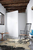 A traditional style rocking chair is juxtaposed with a 1960s style metal chair in this sitting area with a rustic beamed ceiling