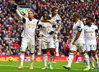 Sunday, 23 February 2014<br /> Pictured: Swansea City players celebrate with Wilfried Bony after he scores from the penalty spot<br /> Re: Barclay's Premier League, Liverpool FC v Swansea City FC v at Anfield Stadium, Liverpool Merseyside, UK.