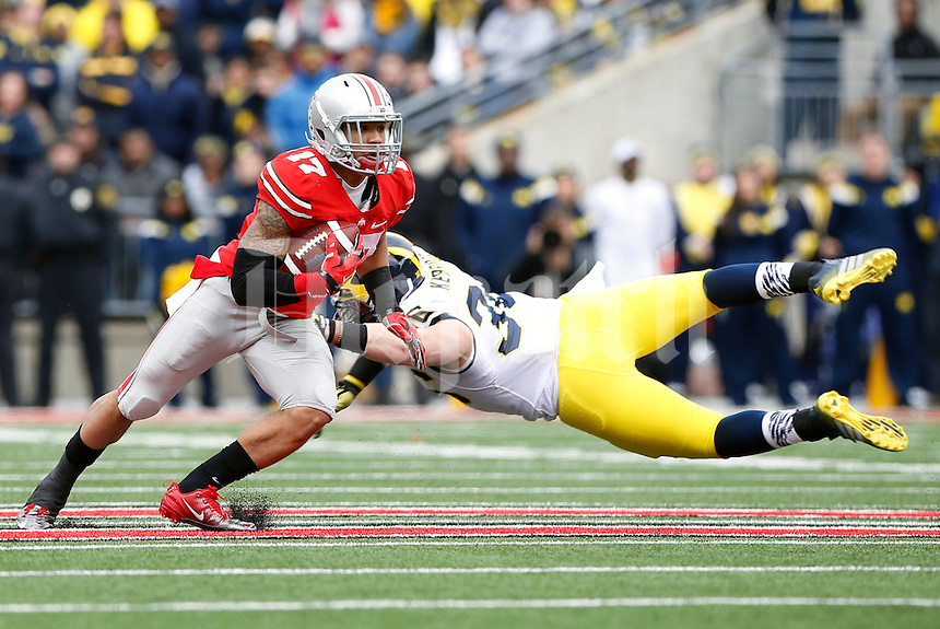Ohio State Buckeyes running back Jalin Marshall (17) eludes the tackle from Michigan Wolverines fullback Joe Kerridge (36) during the 1st quarter of the NCAA football game at Ohio Stadium on Nov. 29, 2014. (Adam Cairns / The Columbus Dispatch)