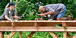 Jaimye Coleman (left) and Anthony Randle Sr. work on top of a shade structure at Highland Elementary School, part of the playground project. She is a volunteer with Edward Jones and he is the father of first and third grade students at the school. Volunteers from the Pacific Life Foundation, Edward Jones, the Riverview Gardens School District, the Boys & Girls Clubs of Greater St. Louis and the community joined KaBOOM! and transformed an empty site into a kid-designed, state-of-the-art playground at Highland Elementary School on Saturday August 18, 2018. The playground - designed from students' drawings - will give more than 400 kids a safe place to play. KaBOOM! is a national non-profit dedicated to bringing balanced and active play into the daily lives of all kids.  Photo by Tim Vizer