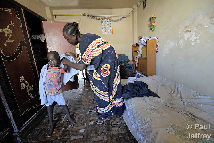 Mery Deng Makwi helps her 5-year old son Riko get dressed for school in her apartment in the Abbasia neighborhood of Cairo, Egypt. The entire family fled fighting in southern Sudan seven years ago. Riko and his two siblings go to school with help from a UN-funded program of Catholic Relief Services to provide education stipends to political refugees in Egypt.