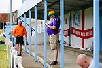 A fan checking his phone at half time. Yorkshire v Parishes of Jersey, CONIFA Heritage Cup, Ingfield Stadium, Ossett. Yorkshire's first competitive game. The Yorkshire International Football Association was formed in 2017 and accepted by CONIFA in 2018. Their first competative fixture saw them host Parishes of Jersey in the Heritage Cup at Ingfield stadium in Ossett. Yorkshire won 1-0 with a 93 minute goal in front of 521 people.
