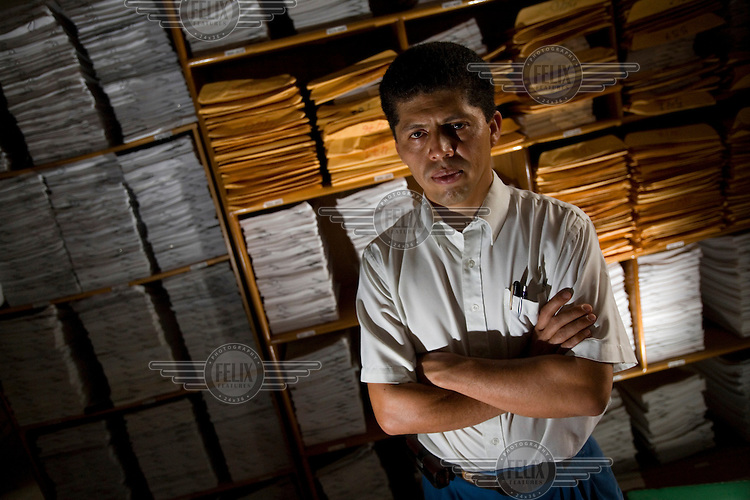 Pablo Fajardo, in his office in Lago Agrio. He is the lead attorney for plaintiffs in a class action lawsuit brought against US multinational Texaco (acquired by Chevron in 2001). The documents he is standing next to are from the case that has been in the Ecuadorian courts since 2003 and relate to the dumping of billions of gallons of toxic materials into unlined pits and Amazonian rivers. In February 2011 the court ruled that Chevron should pay a fine totalling 9.5 billion USD. However, Chevron has stated that the ruling is 'illegitimate and unenforceable' and have started numerous counter proceedings in US courts. Pablo Fajardo won a CNN Hero award for 'fighting for justice' for his tireless work on the case.