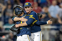 Michigan Wolverines pitcher Tommy Henry (47) is hugged by catcher Joe Donovan (0) after pithing a complete game shutout and defeating the Florida State Seminoles during the NCAA College World Series on June 17, 2019 at TD Ameritrade Park in Omaha, Nebraska. Michigan defeated Florida State 2-0. (Andrew Woolley/Four Seam Images)