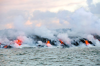 lava enters the ocean at sunrise in Kapoho, Hawaii, along a broad front where a lava river, emanating from fissure 8 (Puka Ewalu) of the Kilauea Volcano east rift zone near Pahoa meets the sea just south of Cape Kumukahi, Kapoho, Puna, Big Island, Hawaii, USA, Pacific Ocean, creating clouds of steam and acid known as laze