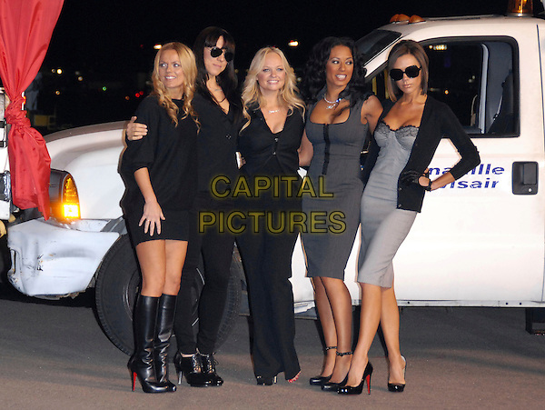 "THE SPICE GIRLS - GERI HALLIWELL, MELANIE CHISHOLM, EMMA BUNTON, MELANIE BROWN & VICTORIA BECKHAM.The Virgin Atlantic announcement of ""Spice One"" , The jumbo jet named in honor of The Spice Girls and their world tour held at LAX in Los Angeles, California, USA..December 12th, 2007                .ginger sporty baby scary posh black grey gray blue dress jacket cardigan sunglasses shades gloves full length hand on hip.CAP/DVS.©Debbie VanStory/Capital Pictures"