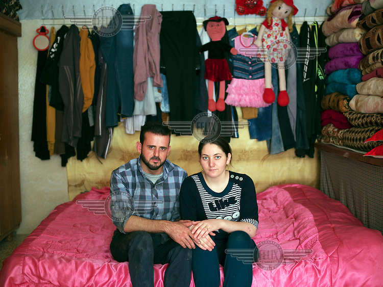A young Yazidi couple, Rahad and Julia, in their home in the Sharia district near Dohuk. They fled Sinjar mountain when ISIS attacked their villages in August 2014. Both their families came to the Sharia district. Julia says: 'We met each other here in December 2015 when he came to my house to repair my family's car. We got married in May 2016. Since then I moved to this house where Rahad's family relocated to. Iraq is my country and I want to go back to Sinjar someday.'