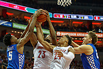 Kentucky Wildcats guard Immanuel Quickley (5) battled with Louisville Cardinals center Steven Enoch (23) and Louisville Cardinals forward Dwayne Sutton (24) during their game at the KFC Yum Center on Saturday Dec. 29, 2018 in Louisville, Ky.
