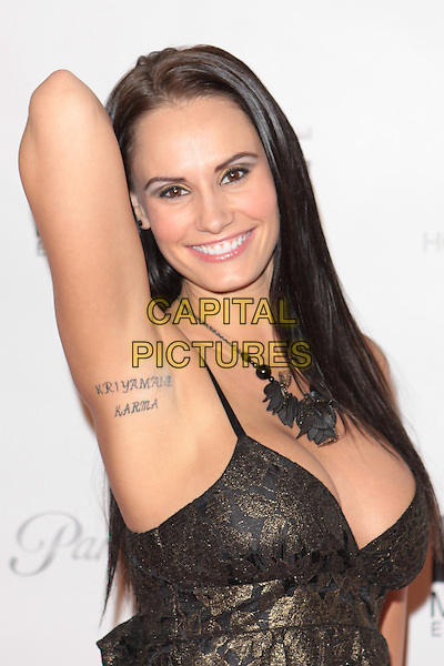 "KRISTEN DELUCCA.""Gridlock New Year's Eve Bash"" held at Paramount Studios, Hollywood, California, USA,  31st December 2009..NYE half length black and gold print pattern dress hand arm armpit up tattoo words necklace smiling .CAP/ADM/TC.©T. Conrad/AdMedia/Capital Pictures."