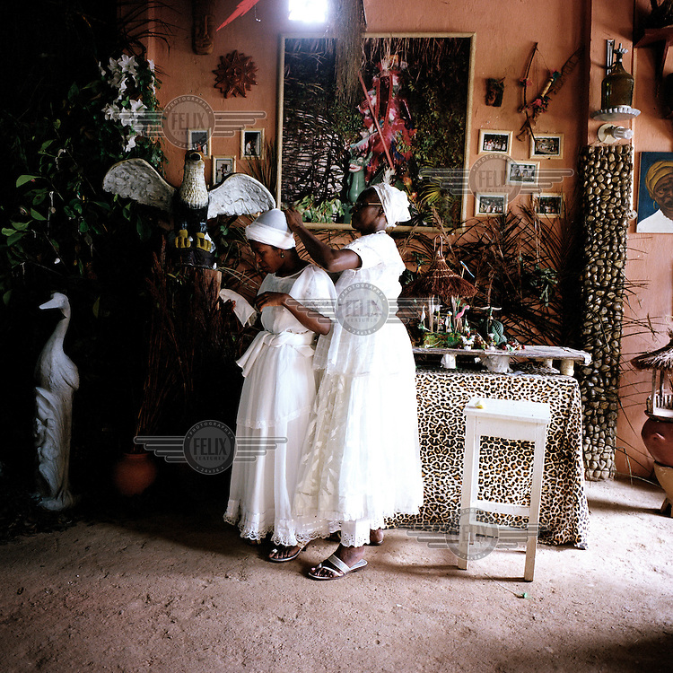 Two woman help each other with their head scarfs at a Candomble Terreiro (Temple).