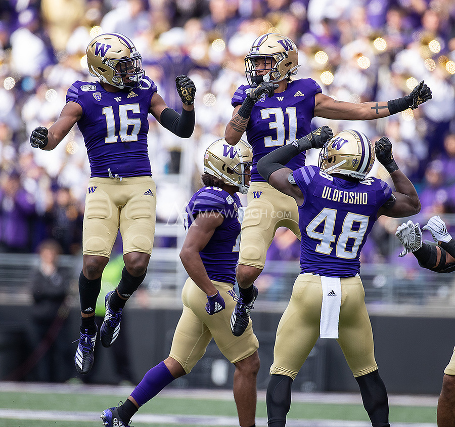 The Husky defense celebrates Cameron Williams' first interception of the game.