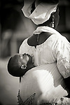 A woman walks through the town of Djibo in northern Burkina Faso, as her baby sleeps quietly strapped to her back.