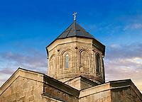 Pictures & images of Gergeti Holy Trinity (Tsminda Sameba) Georgian Orthodox and Apostolic Church cupola close up, 14th century, Gergeti, Khevi province, Georgia (country). At Sunset.