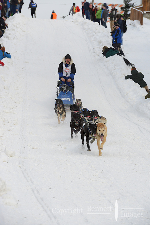 Mushers head down the Cordova hill in downtown Anchorage on day three of the World Championship Sled Dog Races, a highlight of the 2013 Anchorage, Alaska, Fur Rendezvous.