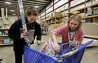 NWA Democrat-Gazette/DAVID GOTTSCHALK  Ela Kisor (left), a junior at Fayetteville High School, and Kelsey Brewer, a senior, sort items Wednesday, March 13, 2019, for shelving at the Habitat for Humanity ReStore of Washington County in Fayetteville. The students are in the Fayetteville High School Ambassadors Service Learning Program and volunteer during school hours at the store. The class also requires an additional 25 hours of community service outside of school hours per semester. The ReStore is open Tuesday through Saturday.
