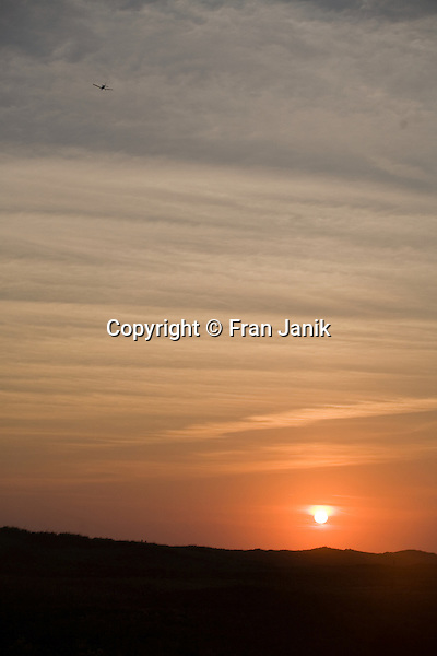 The sun sets on south beach in Martha's Vineyard as an airplane begins it's flight heading west.