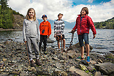 CANADA, Vancouver, British Columbia, portrait of young kids at Brigade Bay on Gambier Island, in the Howe Sound with the Britannia Range in the distance