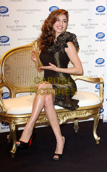 "KELLY BROOK.Launches her new fragrance ""Vivacious"" at a photocall at Boots, Oxford Street, London, England ..November 20th 2008.perfume full length black gold sparkly dress one shoulder ruffled ruffles sitting legs crossed open toe Christian Louboutin shoes bottle .CAP/ROS.©Steve Ross/Capital Pictures."