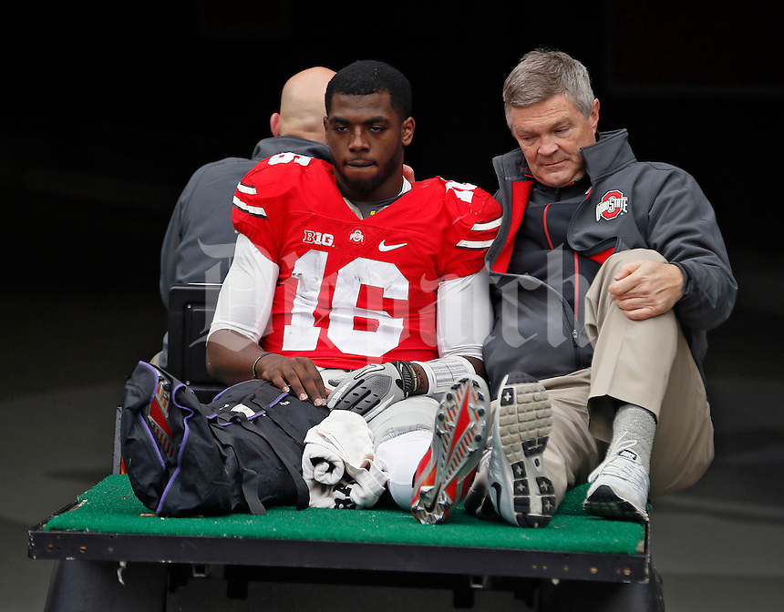 Ohio State Buckeyes quarterback J.T. Barrett (16) leaves on a cart after hurting his right leg or foot against Michigan Wolverines in the 4th quarter of their game at Ohio Stadium in Columbus, Ohio on November 29, 2014.  (Dispatch photo by Kyle Robertson)