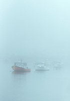 Harbor fishing boats shrouded in heavy fog, Kennebunk, Maine, USA.