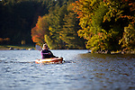 Woman kayaking on a lake in Vermont under fall colors. 2012