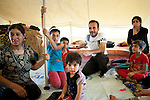 40 year old Ahmed Muhammed Ali (centre rear), a Syrian refugee from Damascus, is seen with his family inside the tent they all share at the Domiz refugee camp in Iraqi-Kurdistan. Ahmed and his family have been living in the camp for four months after leaving Damascus after a bomb destroyed their home; although safe now Ahmed is looking for work in the area around Domiz so he can pay for treatment needed by his youngest daughter, Noorhan (3) (sitting centre front) who has two holes in her heart. The camp, run by the UNHCR and International Rescue Committee, is home to around 4,500 refugees who have fled from the ongoing Syrian civil war with up to 400 new inhabitants arriving every day.  Built on the site of a former Iraqi Army base that was bombed during the 2003 Coalition forces invasion of Iraq, the camp was cleared of cluster bombs and unexploded ordnance by the Mines Advisory Group (MAG), a demining NGO working in Iraqi-Kurdistan.