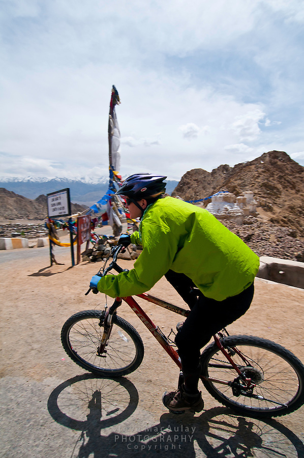 Mountain biker speeds past prayer flags on the highest motorable road in the world, as it approaches Leh.  Himalayan Mountains, Ladakh, India.