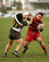 Poneke winger Evan Belford fends off Ories winger Johnny Sola..Wellington Club Rugby - Swindale Shield, Poneke v Oriental-Rongotai at Kilbirnie Park, Wellington, Saturday, 23 May 2009. Photo: Dave Lintott/lintottphoto.co.nz