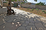 A Palestinian child finds shade under a tree in a garden in the village of Wad Rahal near Bethlehem on 02/06/2010.