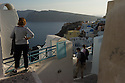 Oia, Santorini, Greece. 08.05.2014. Tourists look out over the Caldera in the whitewashed village of Oia, at the northernmost tip of the island of Santorini. Photograph © Jane Hobson.