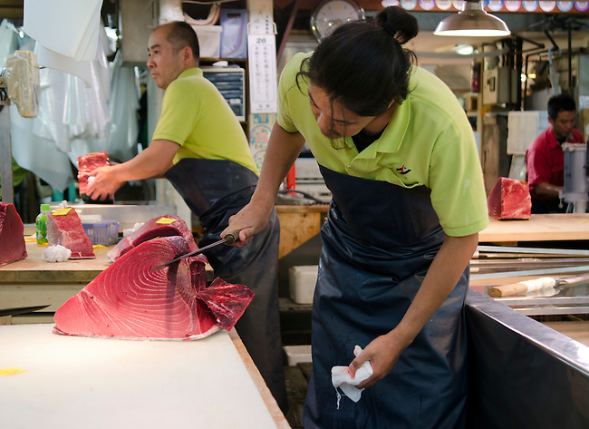 Tuna butcher cuts into large piece of tuna at the Tsukiji Fish Market Tokyo Japan