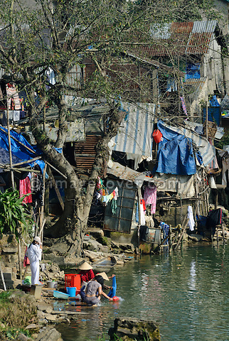 Asia, Vietnam, Hue. Poor peoples housing at the banks of the Huong or Perfume River.