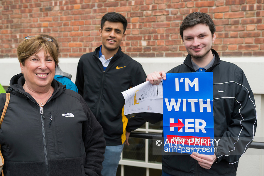 Port Washington, New York, USA. April 11, 2016. RYAN CONNELLY, 20, of Lindenhurst, holding an I'M WITH HER Hillary 2016 poster, and QASIM IQBOL, 18, of Port Washington, are waiting on line to attend a Hillary Clinton, Democratic presidential primary leading candidate, discussion on gun violence prevention with Representative Steve Israel, and activists who lost family members due to shootings. Hillary Clinton, the leading Democratic presidential primary candidate, had several Long Island events scheduled this day, and the New York presidential primary is April 19.