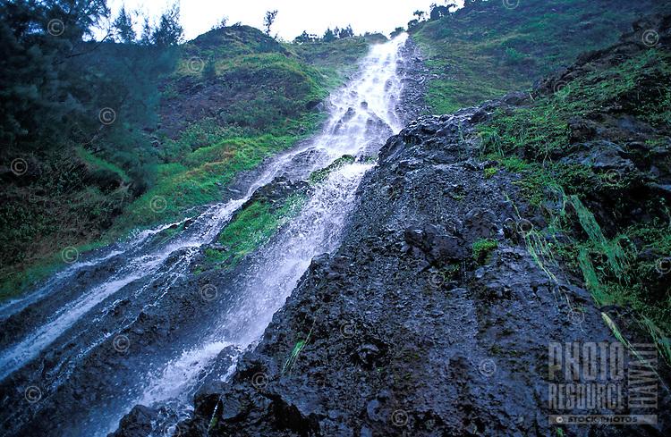A beautiful waterfall cascades down the lush mountainside in Waipio Valley on the Big Island of Hawaii.
