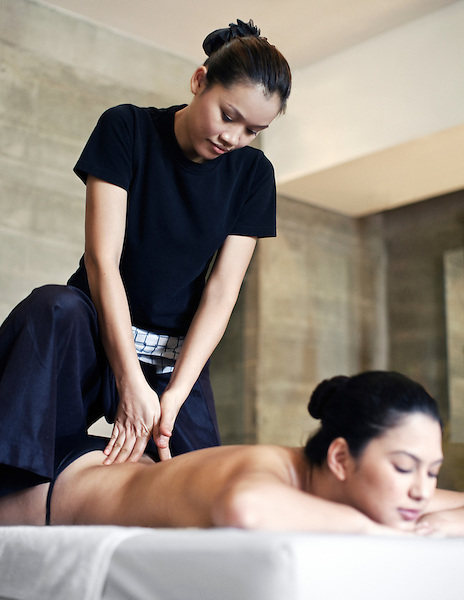 Woman Receiving Massage at Indigo Pearl, Phuket, Thailand. A woman receives an Invigorating Massage in Indigo Pearl's Tuxedo Suite (Room 1309). The Tuxedo Suite is equipped with its own massage room with two massage tables, so guests can enjoy IN-DI-GO Spa's massages in their own suite. Phuket, Thailand.