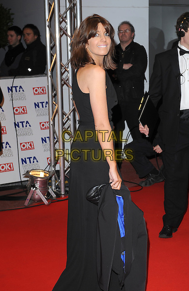 CLAUDIA WINKLEMAN.Arrivals at the 15th National Television Awards held at the O2 Arena, London, England. .January 20th, 2010 .NTA NTAs half 3/4 length maxi dress black side looking over one shoulder.CAP/BEL.©Tom Belcher/Capital Pictures