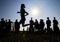 Spring Lake's Georgiana Klem is silhouetted in front of spectators as she approaches the finish line during the Hill and Bale cross country invitational at Fremont Middle School on Saturday. ..Date Shot: 09/12/09