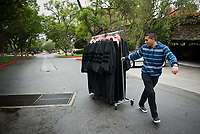 Occidental College student Christian Hernandez '12 takes advantage of a break in the rain to help move formal robes to the President's House. The robes are to be cleaned for inauguration, Oct. 13, 2009. (Photo by Marc Campos, Occidental College Photographer)