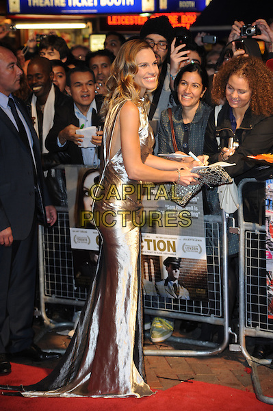 "HILARY SWANK.The 54th BFI London Film Festival screening of ""Conviction"" at Vue cinema, Leicester Square, London, England, UK, October 15th 2010 .LFF full length sleeveless silver shiny metallic wavy hair dress gold long maxi clutch bag smiling signing autographs fans side.CAP/WIZ.© Wizard/Capital Pictures."